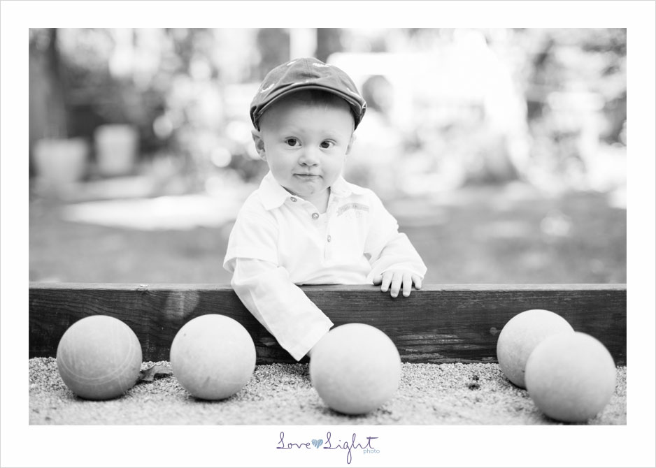 One year old boy playing lawnbowling black and white portrait